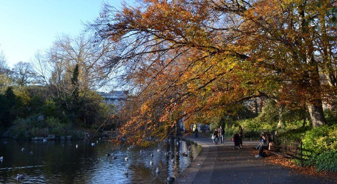 People walking alongside lake in St Stephen's Green Dublin on an autumn afternoon.