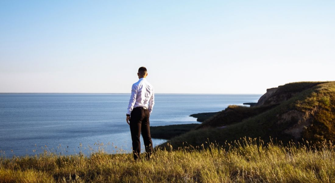A man stands on the edge of a cliff looking out at the sea, pondering the future of work and the possible jobs.