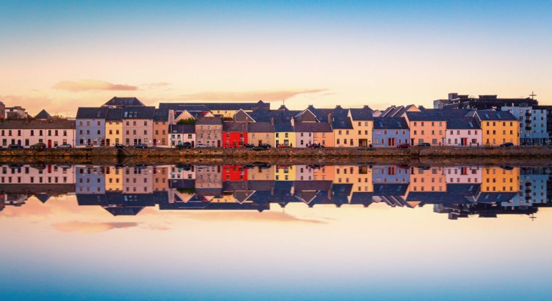 Beautiful view of Galway city from the water with city reflecting on shore.