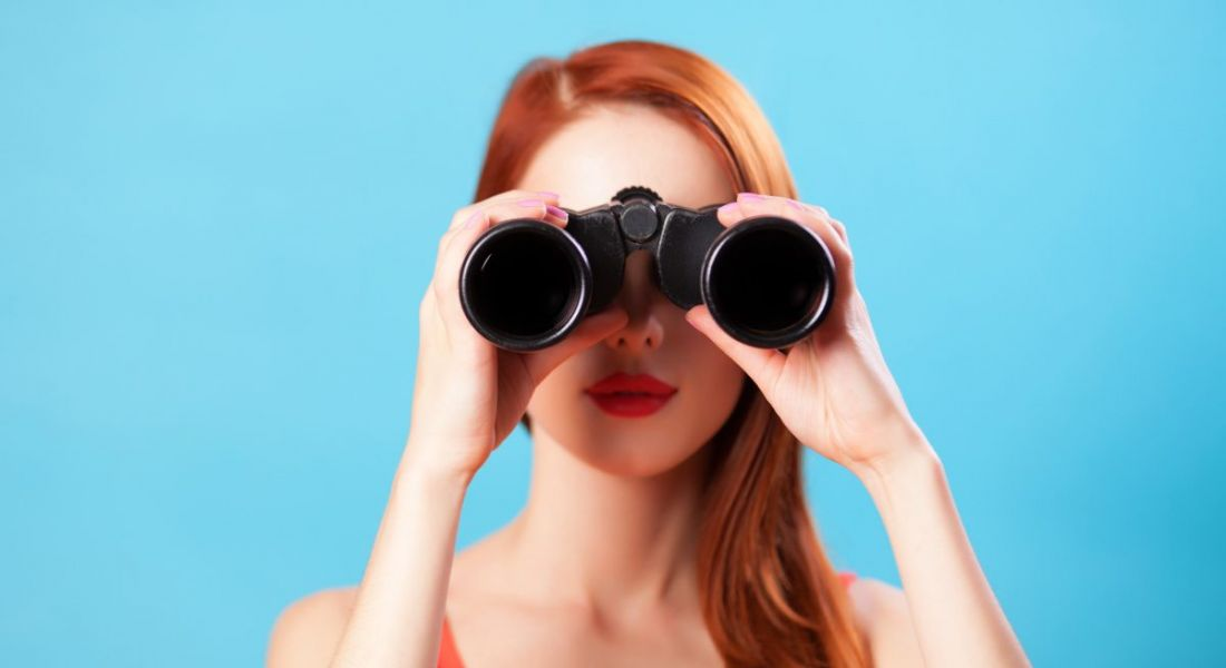A young female jobseeker with red hair looking through a pair of binoculars against a blue background.