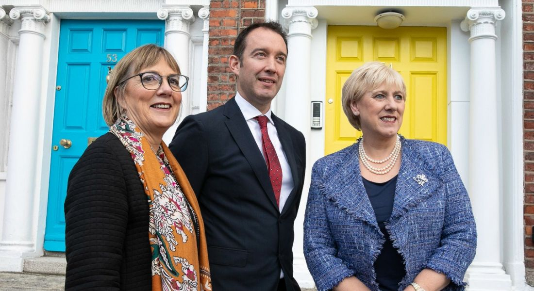 Close up woman and two men looking off into the distance on a blustery Dublin street with a bright yellow door in the background.