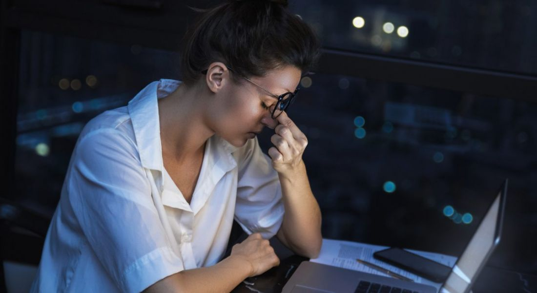 A female employee looks exhausted as she pinches her nose due to work-related stress in a dark room in front of a laptop.
