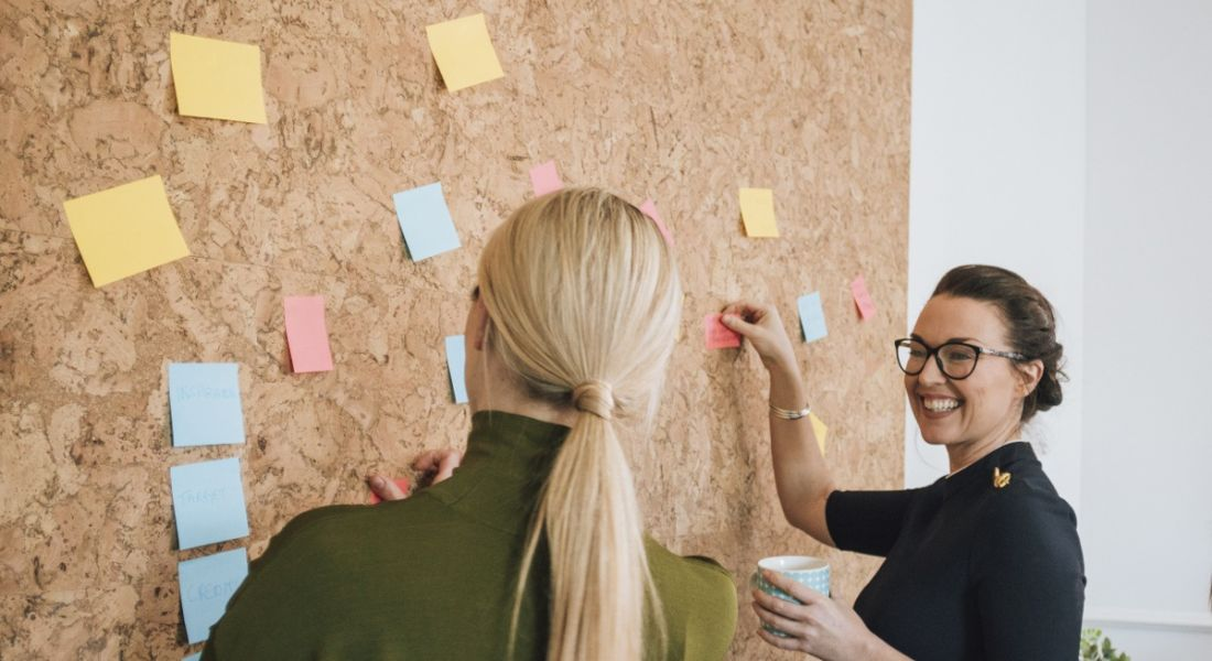Two women standing at a cork board, putting up post-its and smiling. They look like they have great productivity tips.