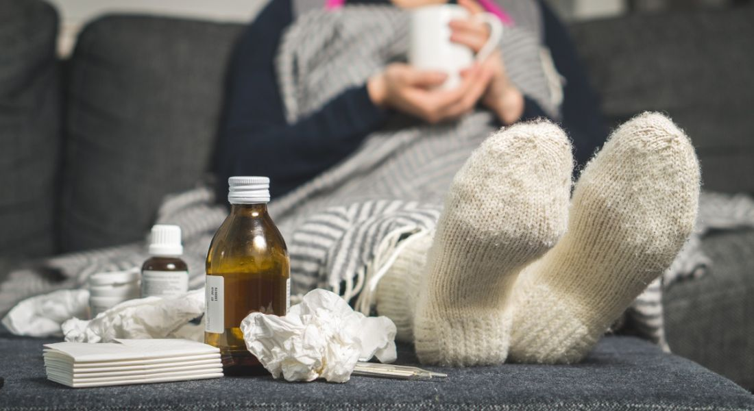 View of sock-clad feet of someone who is sick surrounded by crumpled tissues and cough syrup bottles.