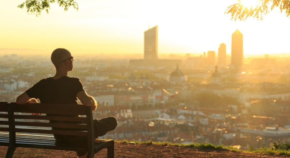 Bald young man in sunglasses sitting on bench on mountainside overlooking the sunrise light pouring over a cityscape.