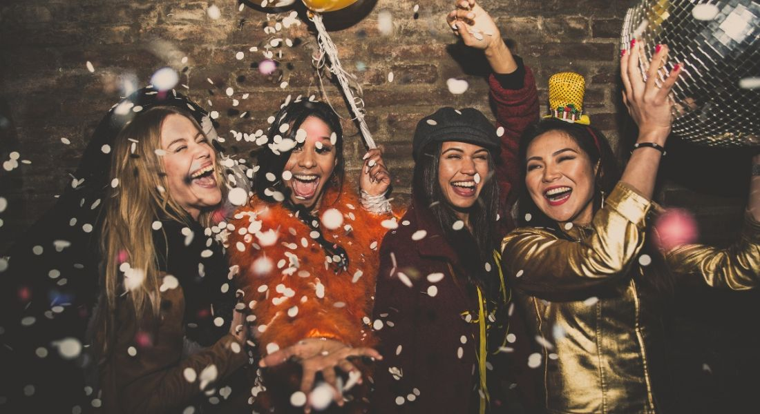A group of young smiling women celebrating on a night out surrounded by confetti. There is a grey brick wall behind them.