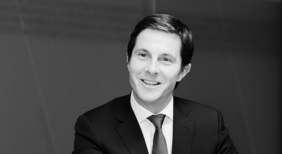 A black and white photo of a smiling man in a formal suit. He is the financial services advisory lead in EY.