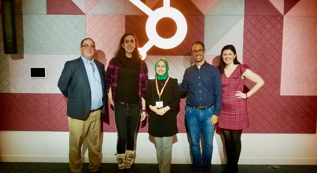 Five diverse people stand in a row smiling in front of the HubSpot logo following a diversity and inclusion event.