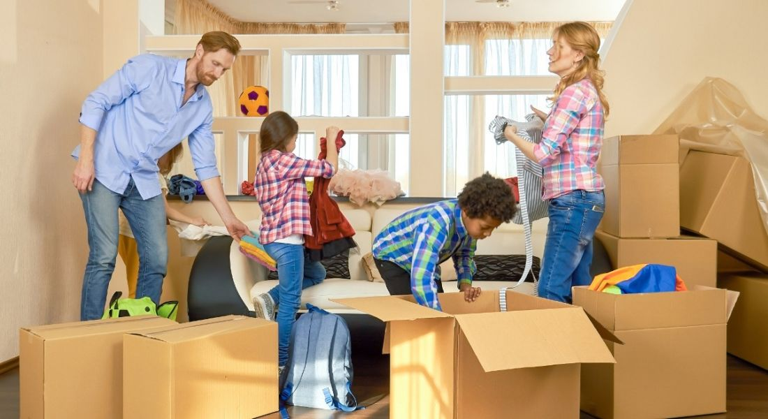 Two adults relocate with children. They're in in a house surrounded by boxes they're unpacking with their two kids.
