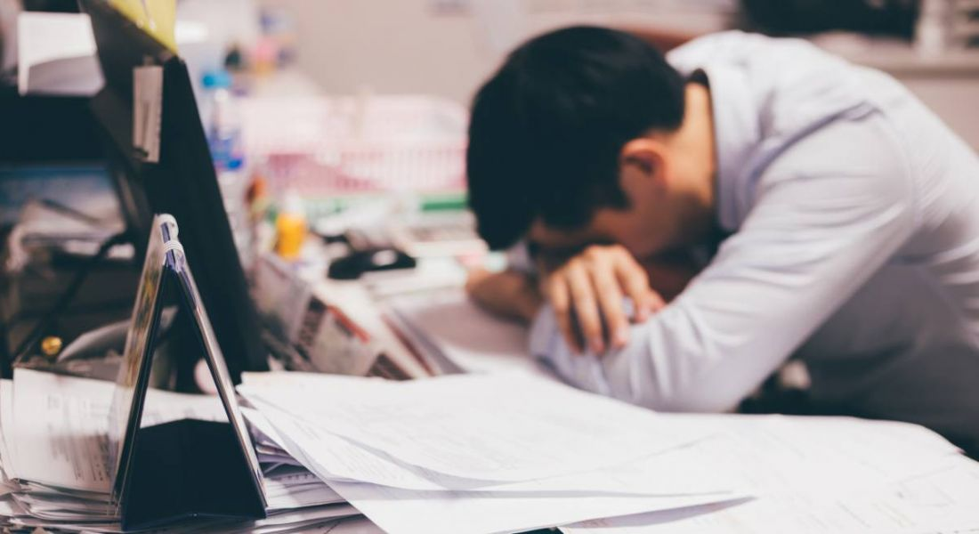A man in an underperformance rut. His head is resting on his arms on a messy desk and he is bored at work.
