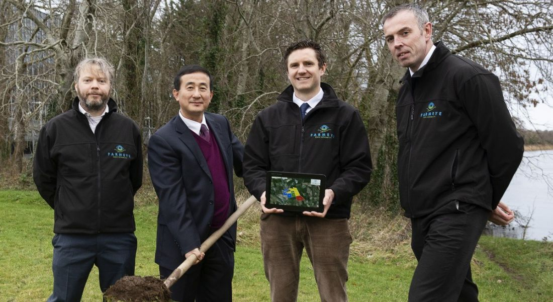 Four men in a field with one holding a shovel of soil.