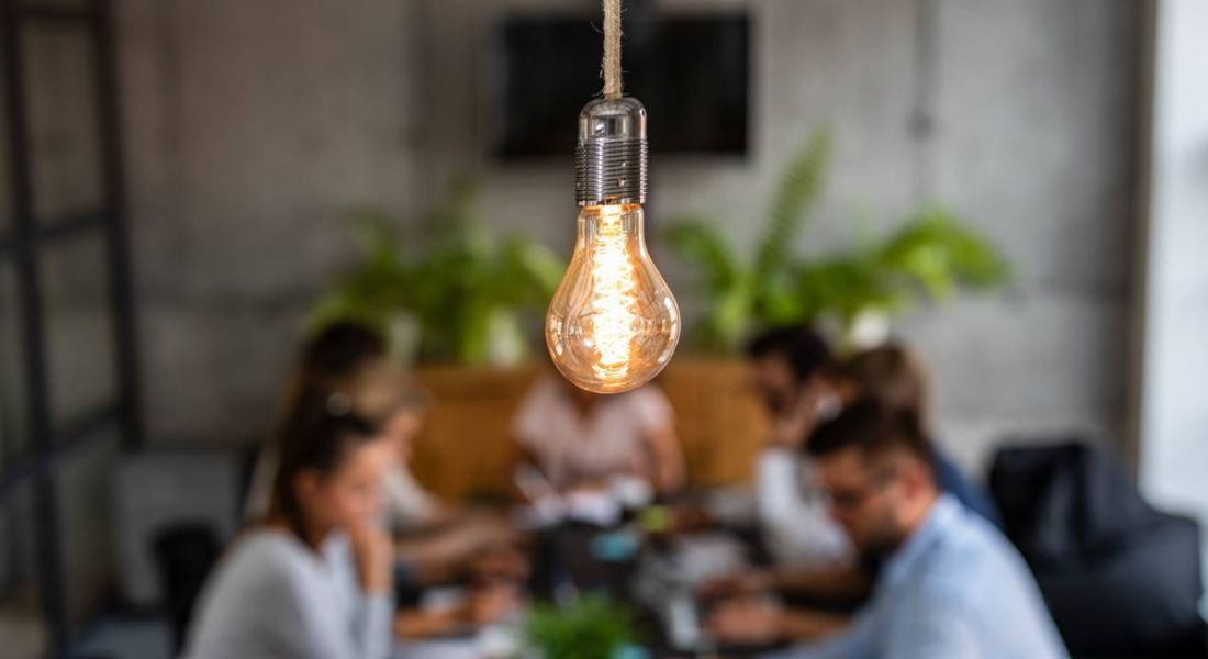 exposed lightbulb in focus in centre foreground with group of young business people working in the background.