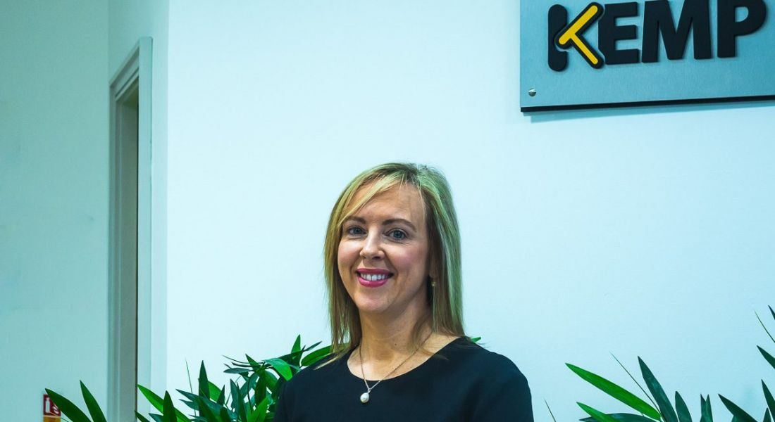 A blonde woman smiling in an office with the Kemp Technologies logo in the background on the wall.