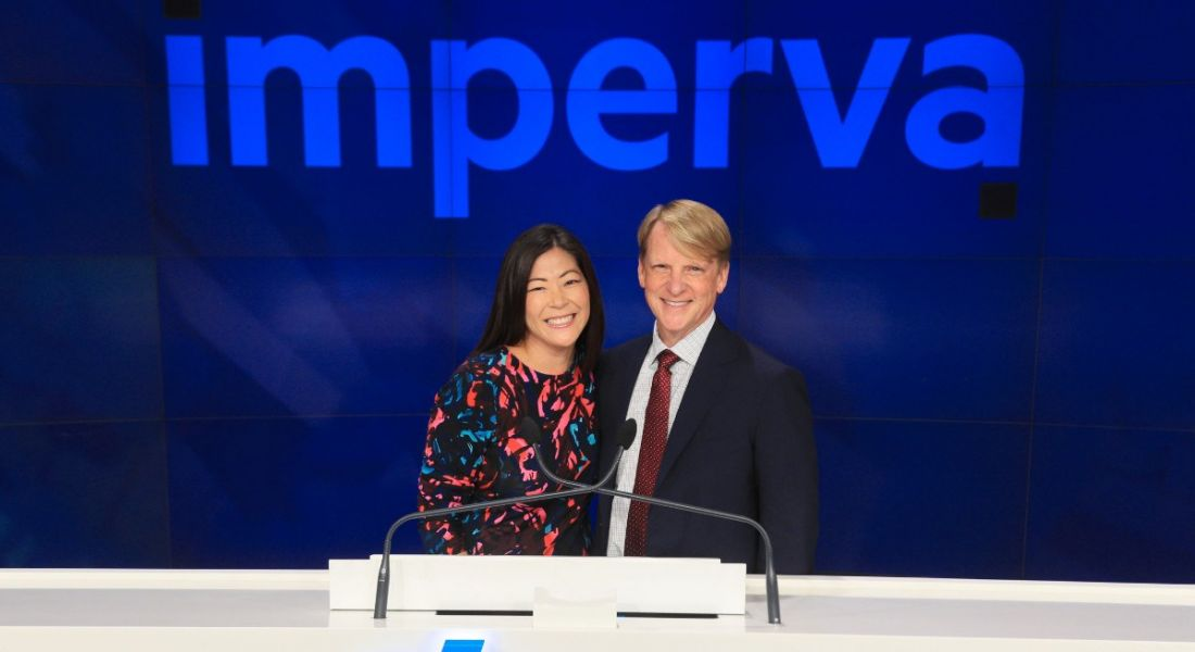 A brunette woman standing next to a blonde man. Both are smiling while standing against a cerulean wall with the Imperva logo on it.