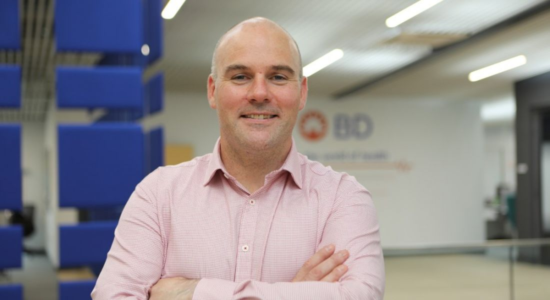 A smiling, middle-aged bald man in a light pink shirt standing in BD. The BD logo is on the wall behind him.