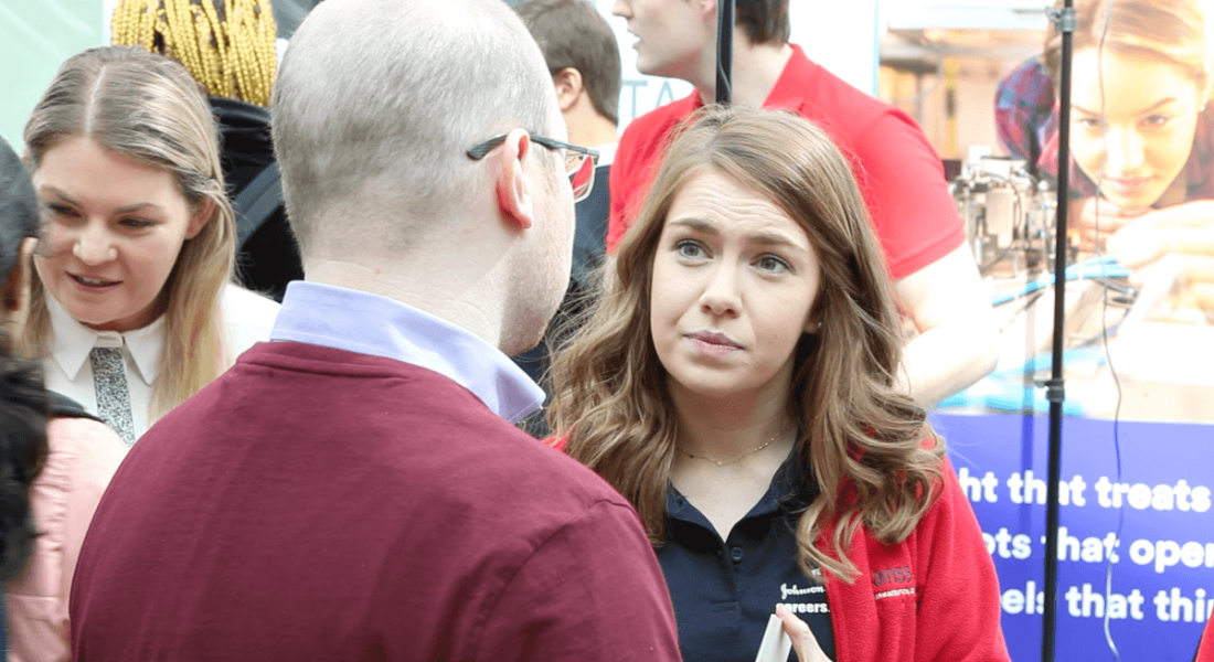 A young woman in a Johnson and Johnson jacket speaking to a man about the biopharma industry.
