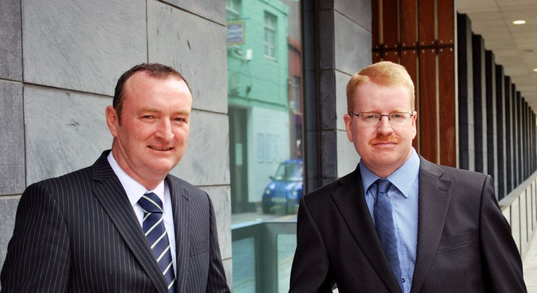 One dark-haired man and one red-haired man in suits stand outside a building.