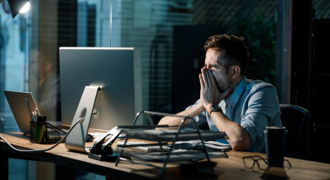 A man at a desk in a dark office covering his face in frustration. He is overworking and feeling burnt out.