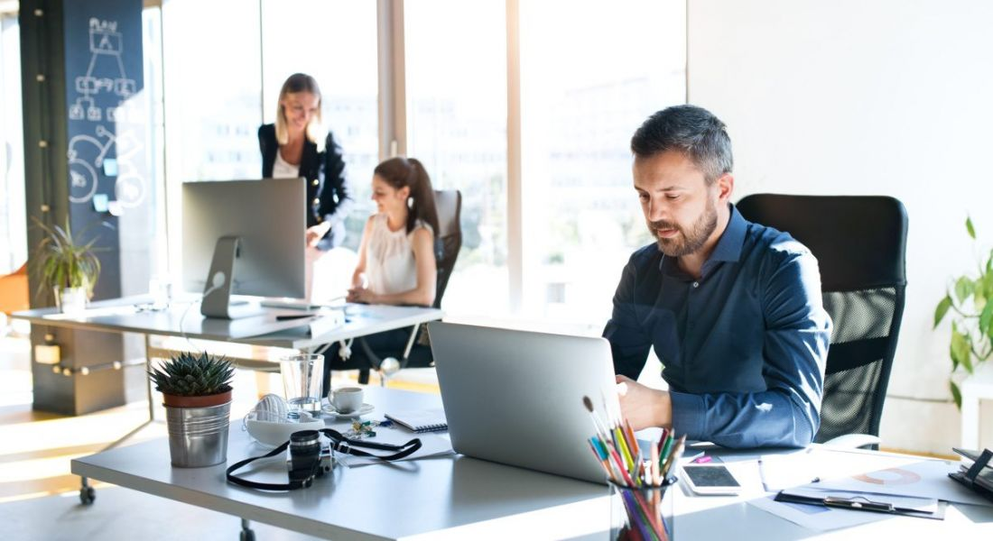 A man at a desk in a bright office with two female workers in the background. They are having a good employee experience.