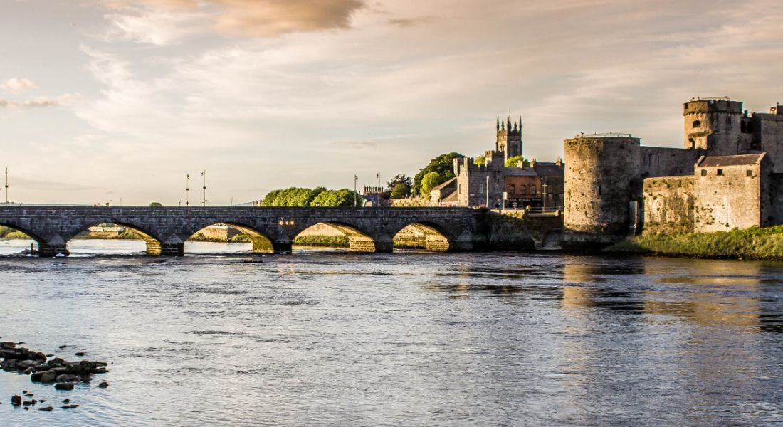 A picturesque view of Limerick from across a river with a bridge and a castle in the background.