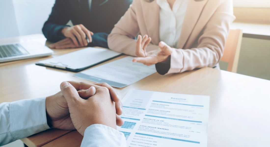 The perspective of an interview candidate as two people ask questions over a table with his CV.