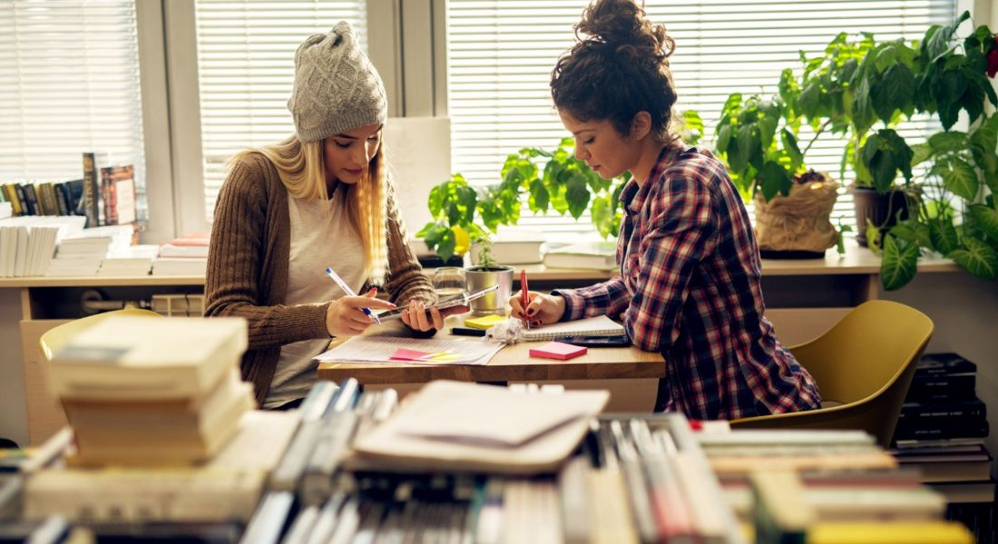 View of two women at a small desk holding highlighters and pens poring thoughtfully over their CVs surrounded by stacks of books.