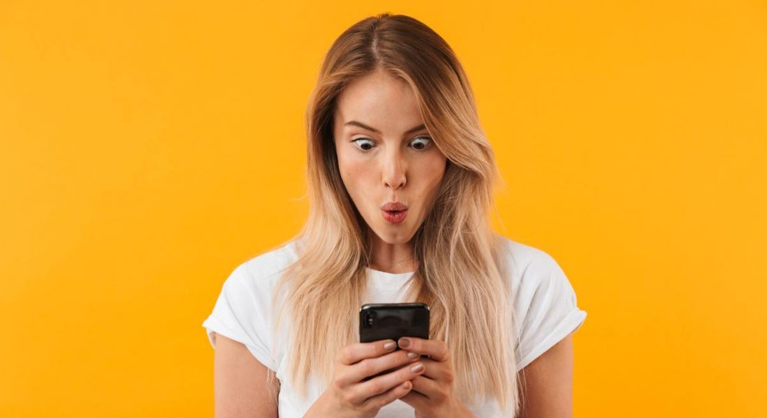 A young woman with long blonde hair looking down at her phone in shock about the amount of sci-tech jobs, against bright yellow background.