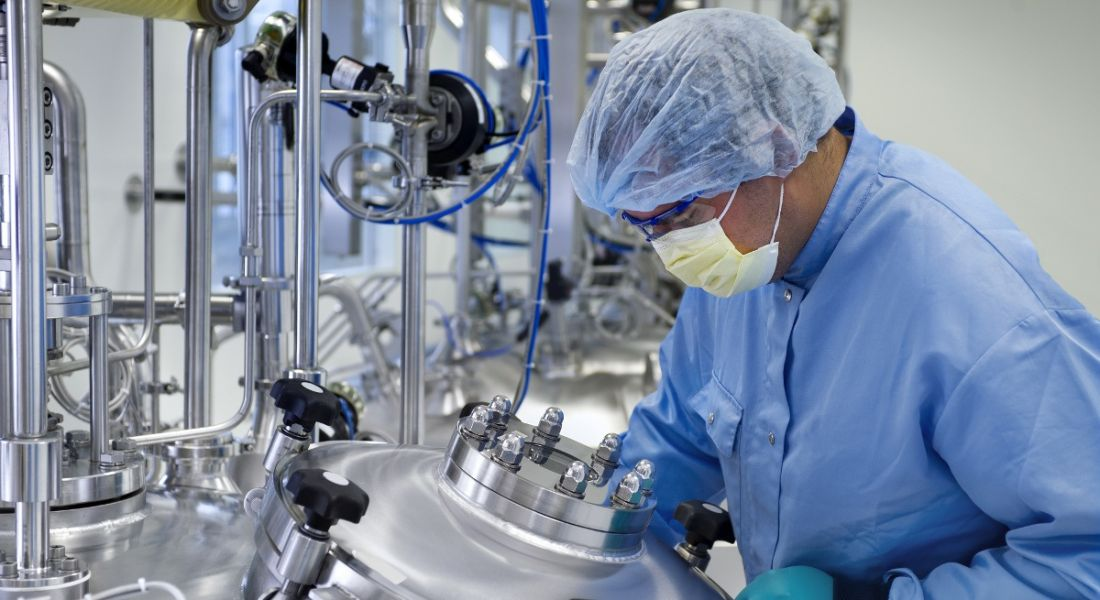 A man in a lab coat, mask and hair net in a biopharma manufacturing facility lab.