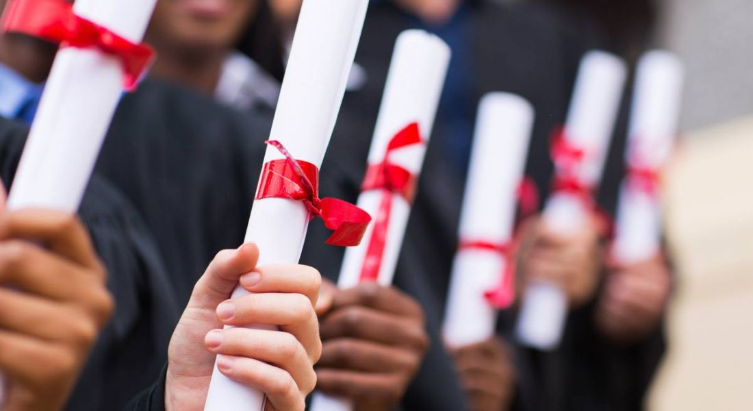 Representing advice for graduates is a close-up on a row of hands holding scrolls tied with red ribbon.