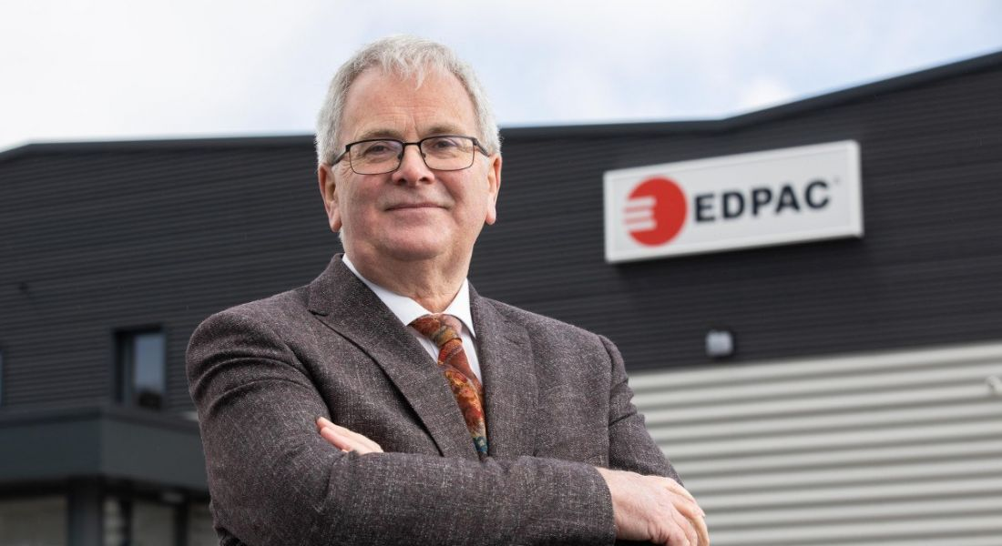A grey-haired man with glasses wearing a suit stands outside an EDPAC facility.