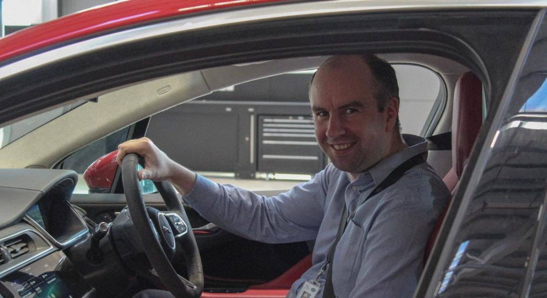 A man in a light blue shirt wearing a seatbelt in a car smiling at the camera.
