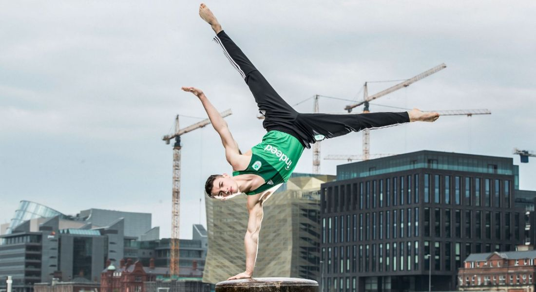 An Irish Olympian gymnast stands on one hand on a dock in Dublin's Silicon Docks.