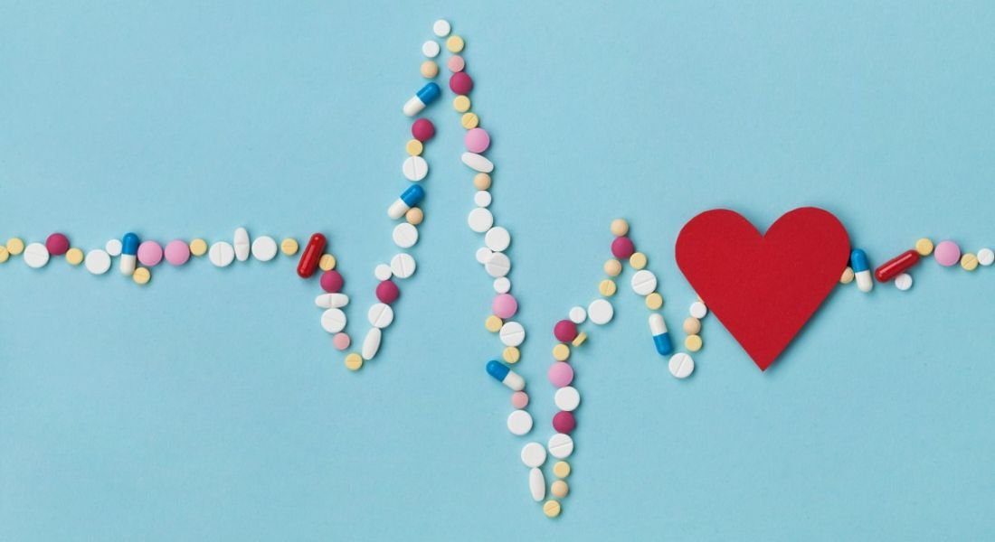 Cardiogram made of colourful pills and a red paper heart, depicting a life sciences and pharma concept.