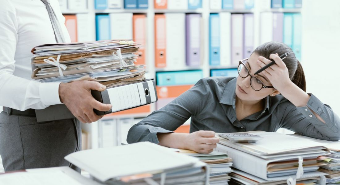 An overworked female office worker resting on a huge pile of files while a manager brings more to her desk.