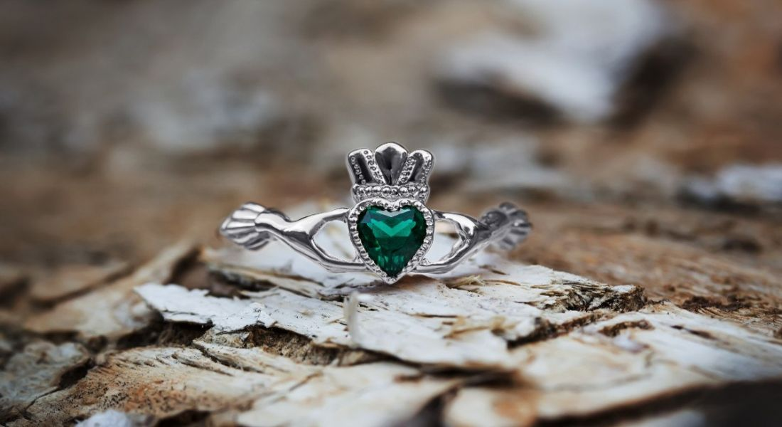 A Claddagh ring with an emerald jewel rests on a rocky beach.