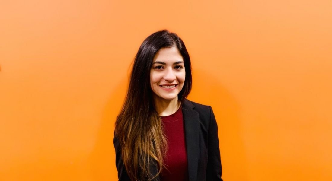 A young woman in a dark business suit standing against a vibrant orange wall smiling at the camera.