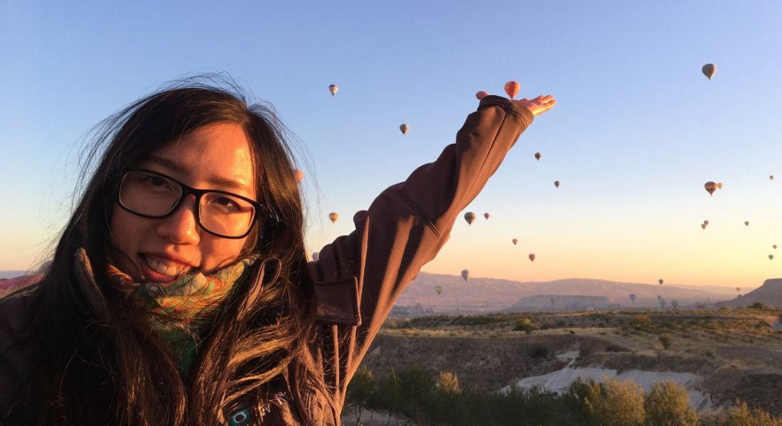 A close-up of a young woman with her arm outstretched behind her at hot air balloons. She works at New Relic.