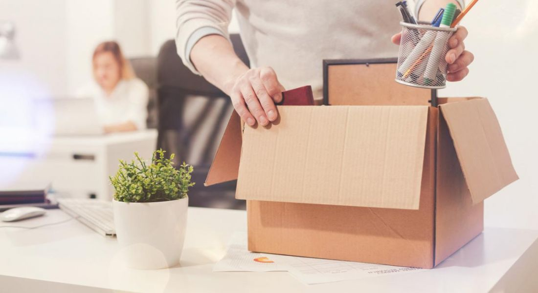 A close-up of an employee holding a box of their things from their desk because they have just quit their job.