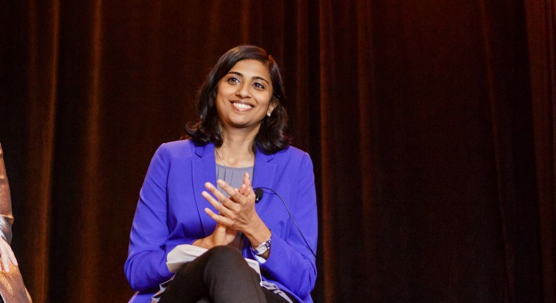 A young woman in a blue blazer sitting on a stage smiling. She's speaking at a conference about the gender pay gap.