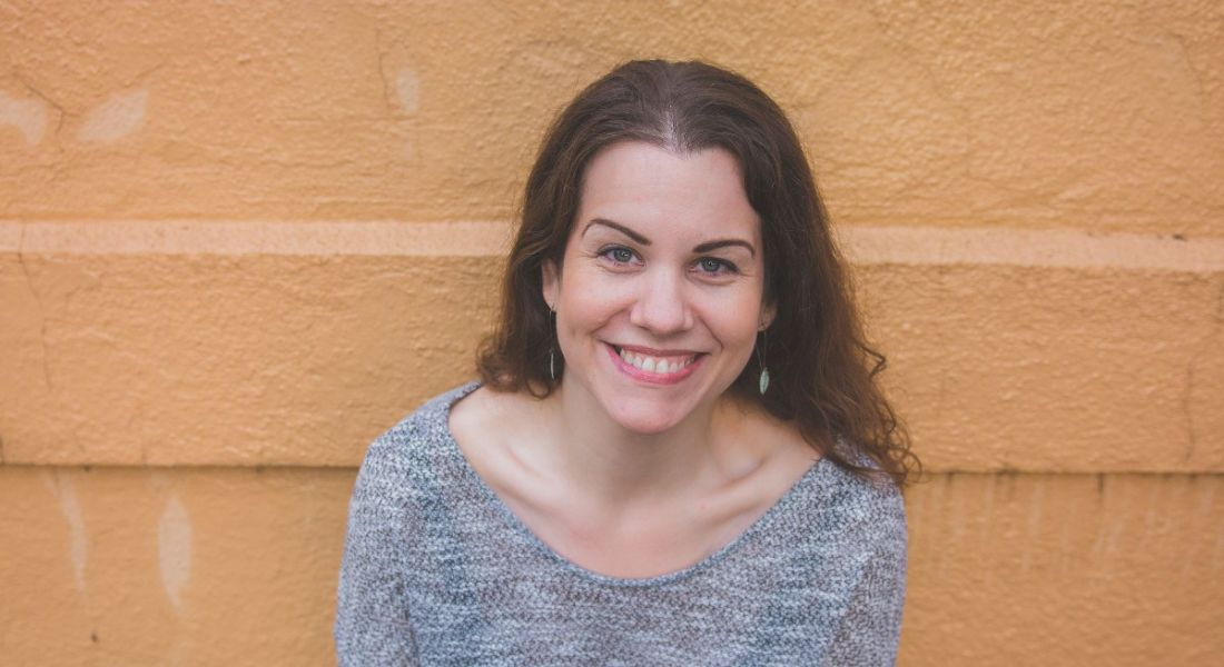 A woman with brown hair smiling against a bright orange wall. She is Jennifer Crow, an expert on grief in the workplace.