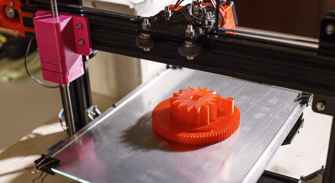 Image of an industrial 3D printer making a circular orange part during manufacturing process.