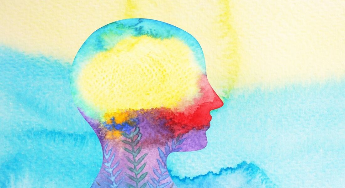 watercolour image of human head with pale yellow and blue as predominant colours, symbolising mental health.