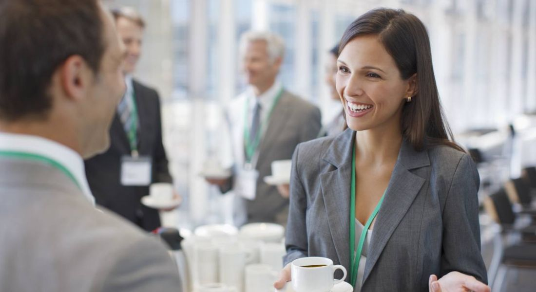 A woman dressed in business attire holding a cup of coffee, smiling and networking with a man.