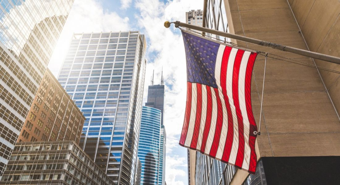 View from below an American flag billowing against the backdrop of a glittering, chrome metropolitan landscape.