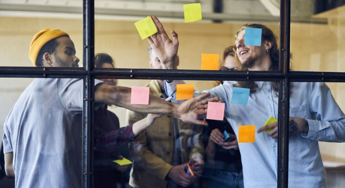 Group of young employees crowded around a window putting up coloured post-it notes and planning how to complete their latest task.