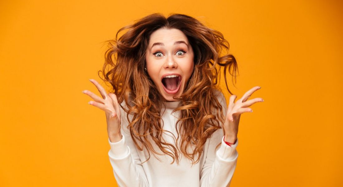 Woman jumping up with arms out in happy surprise with brunette curled tresses lifting into the air against orange background.