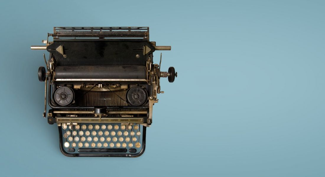 Vintage black typewriter against blue background.