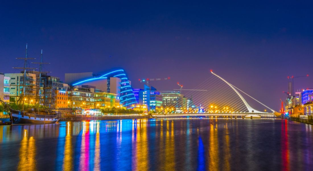 View of Dublin city's Samuel Beckett bridge, Convention Centre and metropolitan skyline at night reflecting on the Liffey River.