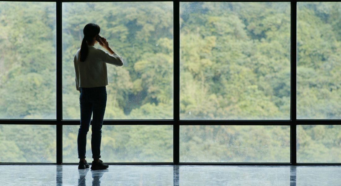 Silhouette of woman on phone looking at trees through tall ceiling-to-floor glass windows contemplating work-life balance.