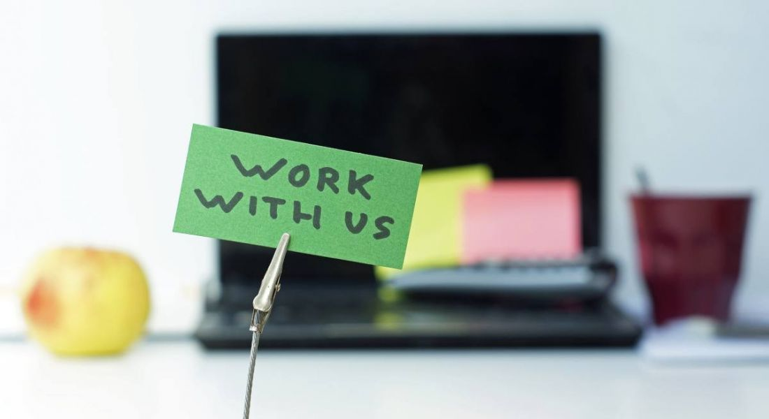 A clip holds a green note in place that reads 'Work with us'. In the blurred background, we can see a laptop and coffee mug.